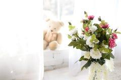 在花瓶的花在与混凝土墙的木地板上背景的 库存图片
