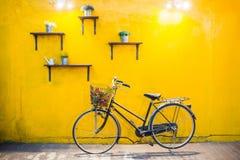 在葡萄酒黄色墙壁上的葡萄酒自行车 库存图片