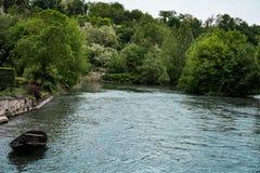 在蓝色河的偏僻的小船 库存照片