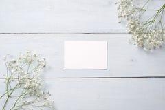 在蓝色木书桌上的空插件有花的 您的祝贺的空的贺卡与复活节、母亲或者妇女天,春天 库存照片