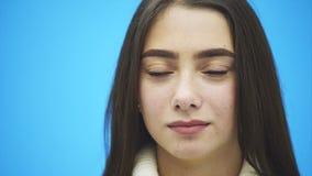 在蓝色背景的年轻俏丽的女孩身分 在这时间她在一件白色温暖的毛线衣打扮 微笑 股票视频