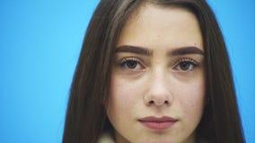 在蓝色背景的年轻俏丽的女孩身分 在这时间她在一件白色温暖的毛线衣打扮 看 影视素材