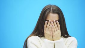 在蓝色背景的年轻俏丽的女孩身分 在这时间她在一件白色温暖的毛线衣打扮 面孔结束 股票录像