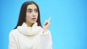 在蓝色背景的年轻好企业女孩身分 在此期间,她在她有一个想法,她显示了它用手 影视素材