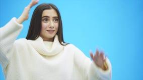 在蓝色背景的美好的少女身分 在这时间她在一件白色毛线衣打扮 长的黑色 股票视频
