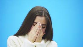 在蓝色背景的美好的少女身分 在这时间她在一件白色毛线衣打扮 长的黑色 影视素材