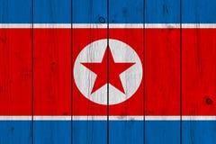 在老木板条绘的北朝鲜旗子 免版税图库摄影
