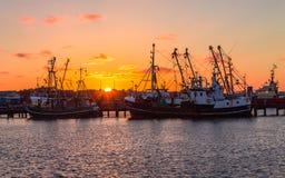 在老拖网渔船的美好,全景在勒姆岛在日落期间的Rømø Havn港口  在背景老船, 库存照片