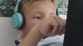 在耳机的乏味孩子观看某事在触摸板的 股票录像