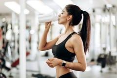 在黑体育衣裳打扮的苗条女孩是从瓶的饮用水在健身房 免版税库存照片