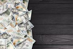 在黑木背景的很多美元 免版税库存照片
