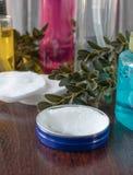 在黑暗的背景的化妆辅助部件,在一个蓝色瓶子的白色奶油 图库摄影