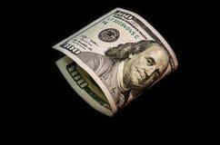 在黑背景的弯曲的美元 免版税库存照片