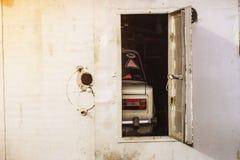 在铁车库后的开门的老汽车 库存图片