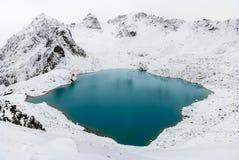 在雪中的蓝色湖在山 库存照片