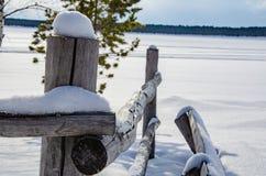 在雪的老土气篱芭 雪熔化 免版税图库摄影