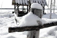在雪的老土气篱芭 雪熔化 库存照片