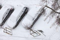 在雪盖的停放的汽车在飞雪顶视图以后 库存照片