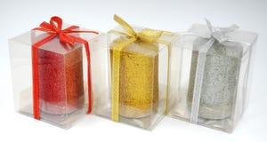 在透明塑料盒的红色,金黄黄色和银灰色蜡烛有丝带的 免版税库存照片