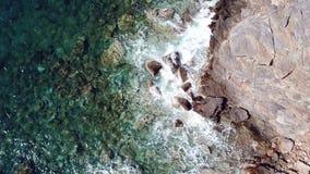在透明的波浪下看法的空中上面在岩石海岸的与沿海岸线的清楚的蓝色水的飞行 股票视频