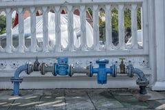 在footpart,寺庙篱芭前面,曼谷泰国的泄漏水管 免版税图库摄影