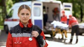 医务人员摆在为照相机的,运输背景的救护车乘员组患者 库存照片