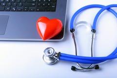 医生工作场所有听诊器、红心、膝上型计算机、rx处方和笔记本的在白色桌上 顶视图 免版税图库摄影