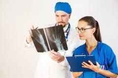 医生和护士看看X-射线的结果,医生在规定治疗,护士写一切 免版税库存图片