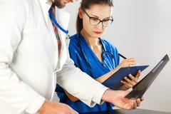 医生看X-射线并且告诉护士规定的什么治疗 免版税库存照片