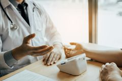 医生解释关于血压给诊所的患者并且提供关于治疗的信息 库存图片