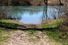 土带领直接地入河的乡下公路使用为降低河船围拢与草和森林植物群落 库存图片
