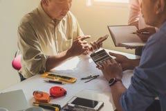 土木工程师或建筑师事务的接近的手使用计算器的计算与工作大楼计划的费用 免版税库存照片