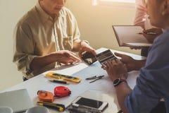 土木工程师或建筑师事务的接近的手使用计算器的计算与工作大楼计划的费用 库存照片