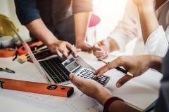 土木工程师或建筑师事务的接近的手使用计算器的计算工作大楼计划的费用 库存照片