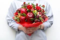 包括石榴、苹果、李子和猩红色玫瑰在妇女的手上的可食的花束白色背景的 库存图片