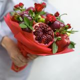 包括石榴、苹果、李子和猩红色玫瑰在妇女的手上的可食的花束白色背景的 免版税库存图片