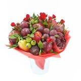包括石榴、苹果、李子和猩红色玫瑰的可食的花束站立在白色背景隔绝的花瓶 免版税库存图片