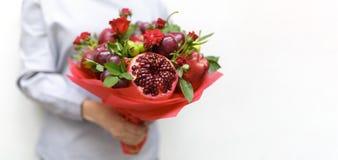 包括石榴、苹果、葡萄、李子和猩红色玫瑰在一名妇女的手上的美丽的花束白色背景的 库存照片