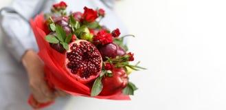包括石榴、苹果、葡萄、李子和猩红色玫瑰在一名妇女的手上的美丽的花束白色背景的 免版税库存照片