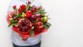 包括石榴、苹果、葡萄、李子和猩红色玫瑰在一名妇女的手上的美丽的花束白色背景的 免版税库存图片