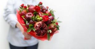 包括石榴、苹果、葡萄、李子和猩红色玫瑰在一名妇女的手上的美丽的花束白色背景的 库存图片