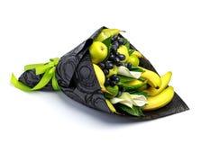 包括香蕉、梨、苹果、石灰和黑葡萄在白色背景的独特的可食的花束 免版税库存照片