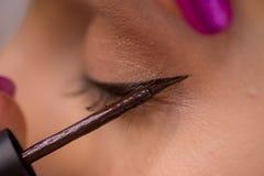 化妆师在妇女的眼睛上把眼睛划线员放在沙龙 库存图片