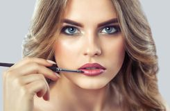 化妆师绘美女的嘴唇,完成在发廊的构成 免版税库存照片