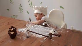 厨师帽子的可爱宝贝舔一个杓子用面粉和戏剧用在桌上的面粉 影视素材