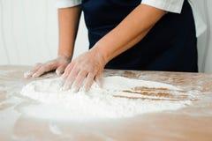 厨师在厨房里准备面团-做面团的过程 库存照片