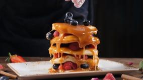 厨师手特写镜头在家倾倒在可口有机薄煎饼之上的有机黑莓早餐或在a 影视素材