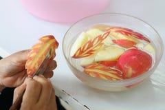 厨师的手,当雕刻在叶子形状时的新鲜的苹果 免版税图库摄影