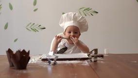 厨师的盖帽的可爱宝贝对桌微笑并且舔从匙子的面粉 股票视频