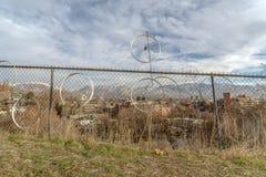 垂悬在生锈的金属篱芭的老自行车轮子外缘 库存图片